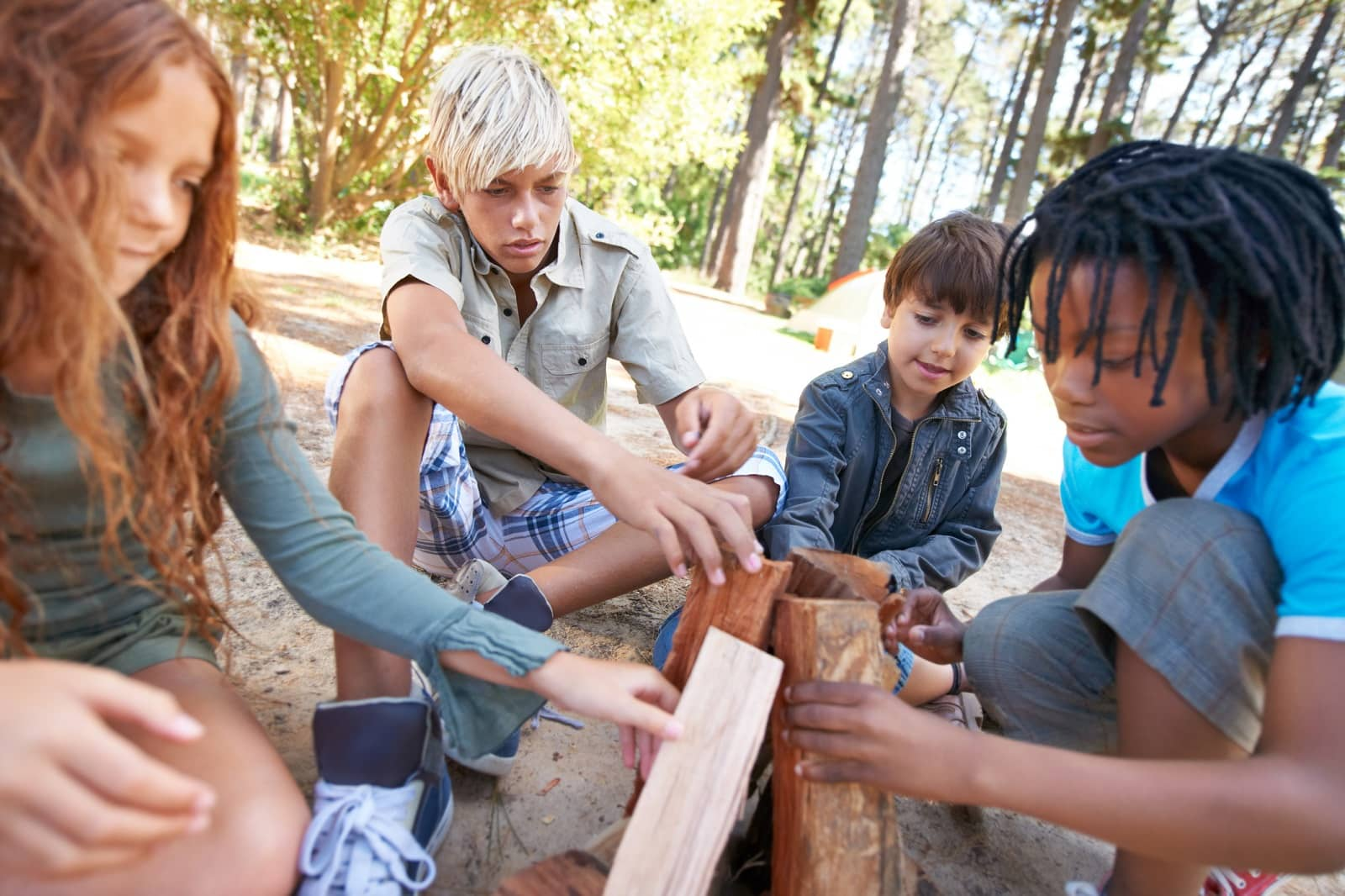 Kids building a fire at camp