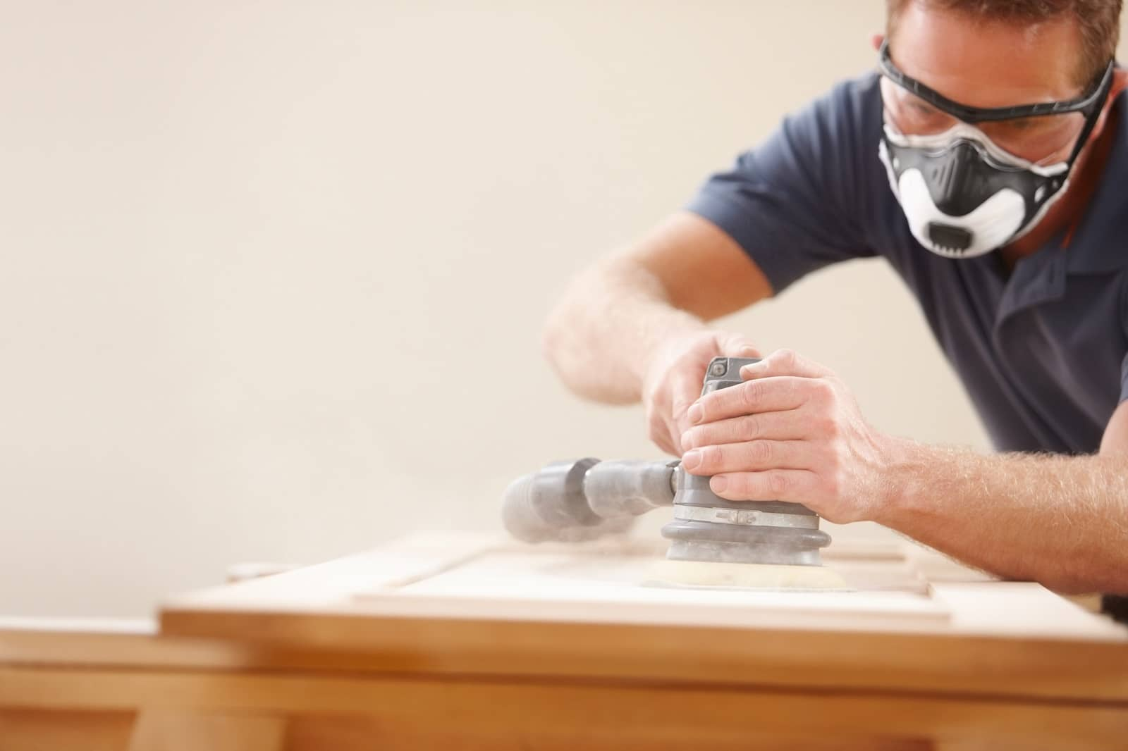Carpenter using an electric sander
