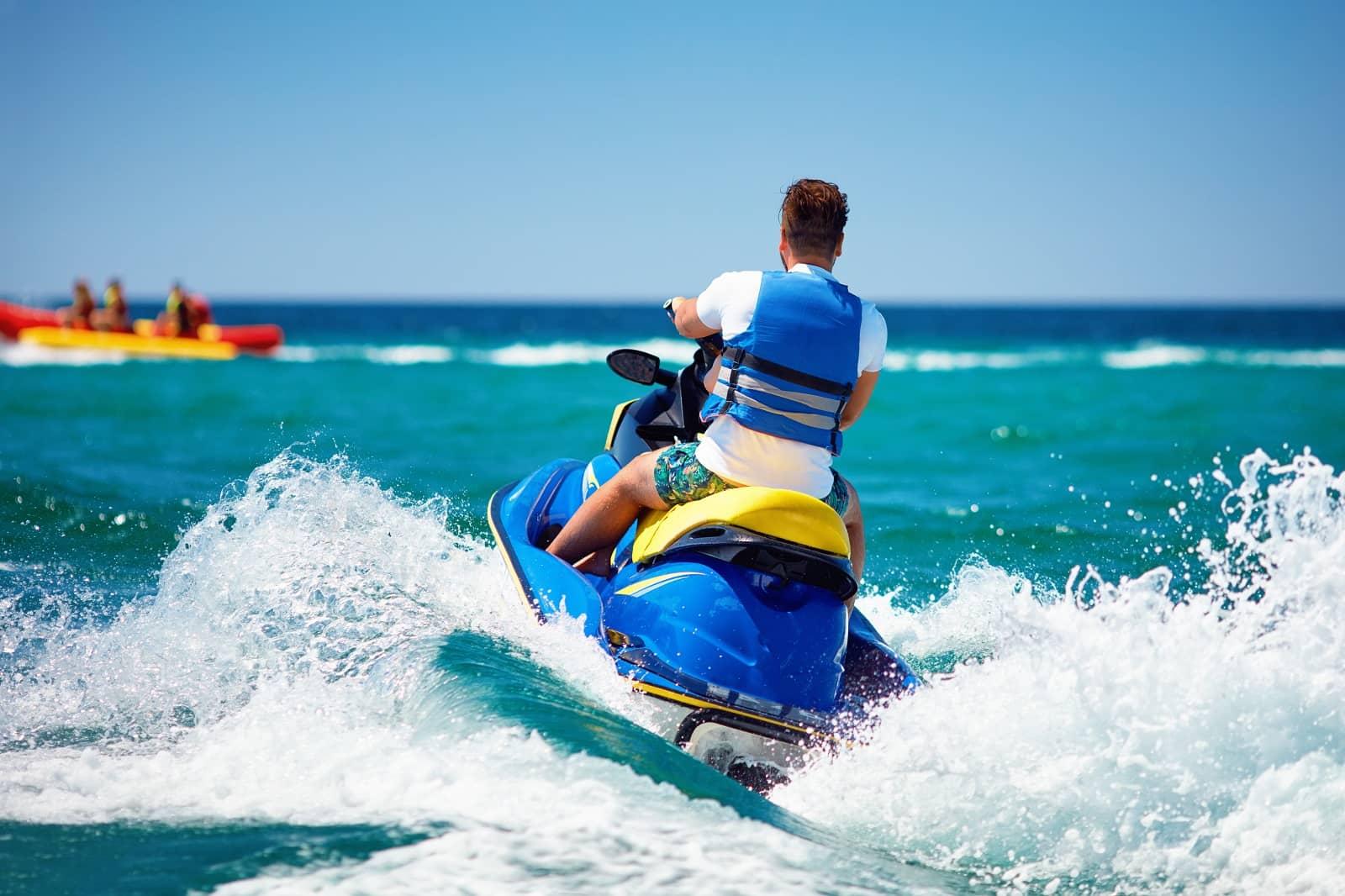 Back view of man riding jet ski