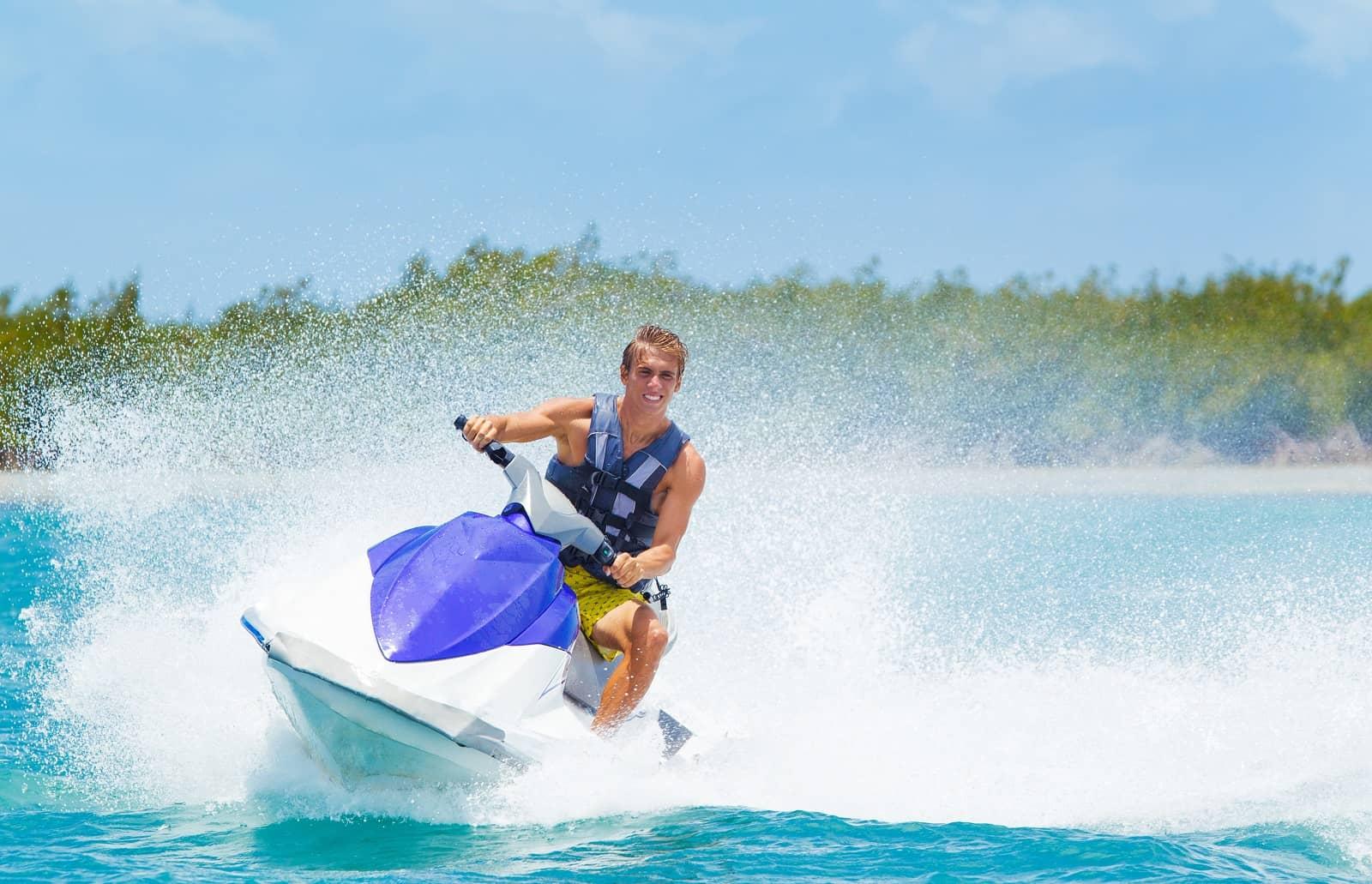 Man turning jet ski on bright blue water