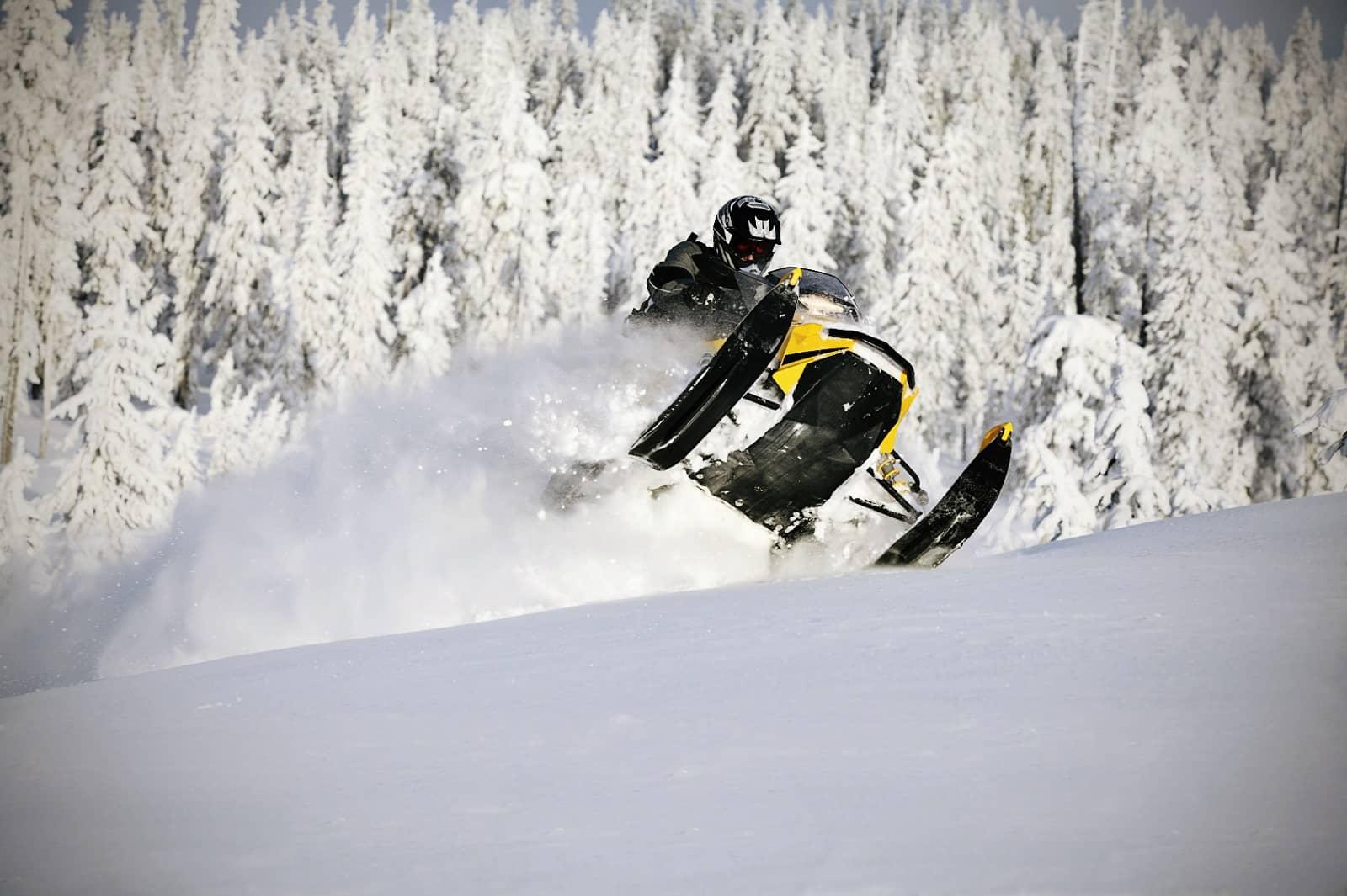 Snowmobile jumping through powdery snow