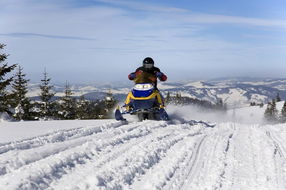 Riding snowmobile on snow covered mountains