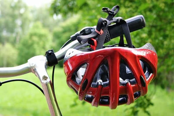 Bicycle helmet hanging on bicycle handlebar