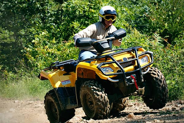 Man wearing helmet and goggles driving yellow ATV