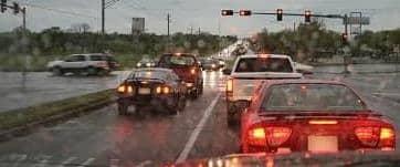 Car brake lights at a traffic light in the rain