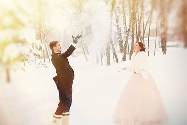 Newlyweds throwing snow during winter wedding